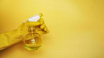 hand i gul gummihandske som håller plastspray foto