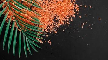 orange havssalt på en svart bakgrund. tropiska palmblad foto
