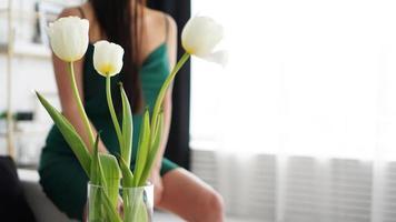 vita tulpaner i en vas. suddig bakgrund - kvinna i en grön klänning foto