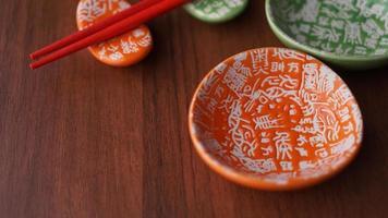 uppsättning keramiska rätter och röda sushipinnar på träbakgrund foto