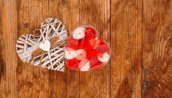 röda och vita rosor och alla hjärtans dag vita hjärta på trä bakgrund foto