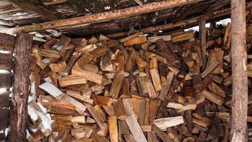loggning i byn. hackade stockar under en baldakin på vintern foto