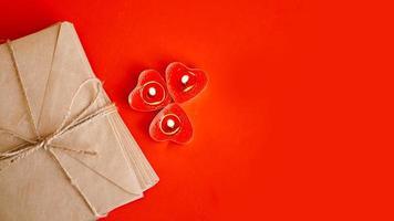 kraftpapper kuvert med röda ljus på en röd bakgrund. foto