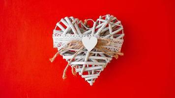 vit handgjord hjärta på röd bakgrund foto