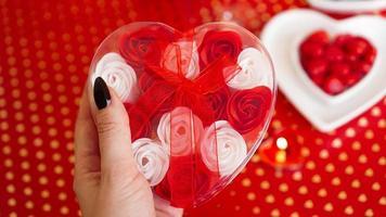 kvinnahänder som håller en presentask i hjärtform med vacker ros foto