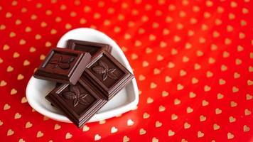 choklad i en hjärtformad tallrik på röd bakgrund foto