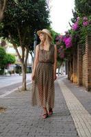 vertikalt foto. en kvinna i en klänning går längs en vacker gata foto