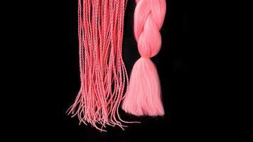 rosa kanekalon hänger på en svart bakgrund foto