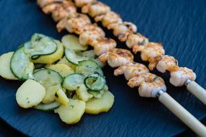 kryddiga vita tigerräkor från grillen med potatisgurkasallad foto