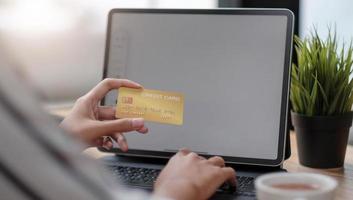 närbild flicka på internet på den digitala surfplattan med kreditkort foto