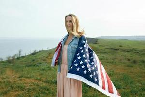 en flicka i en korallklänning och en jeansjacka håller USA: s flagga foto