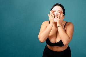 glad plus size tjej gör full split med hudvårdsmask foto