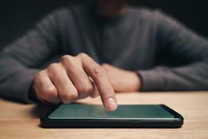 man som använder en smartphone på bordet, söker, surfar, sociala medier foto