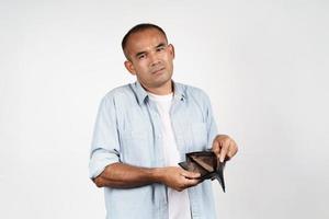 man som håller sin tomma plånbok på vit bakgrund. inga pengar. foto