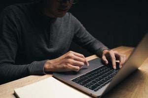 man använder bärbar dator på bordet, söker, surfar, sociala medier. foto
