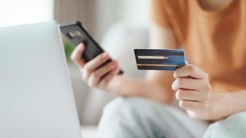 kvinna som håller kreditkort och använder smart telefon för online shopping. foto