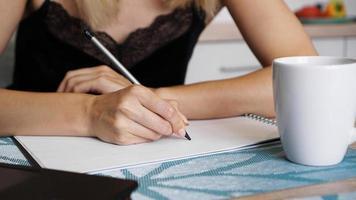 kvinna hand använda blyertsskrivning på klart ark foto