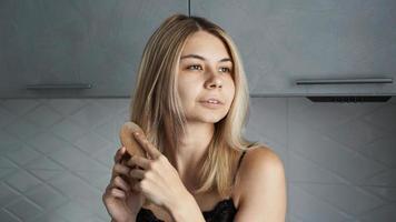 ung vacker kvinna som rätar ut håret foto
