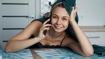 ung kvinna i köket. pratar i telefon och ler foto