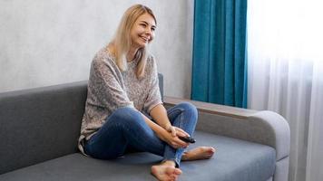 glad kvinna som tittar på tv sitter i en soffa i vardagsrummet hemma foto