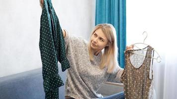 gullig kvinna som väljer sin outfit, håller två klänningar på galgar foto