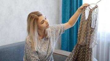 vacker kvinna håller en galge med en klänning foto