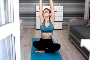 yoga hemma. håll dig lugn. attraktiv ung kvinna som sitter på golvet foto