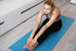 fitness kvinna som sträcker benen hemma foto