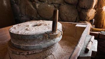 en gammal handkvarn gjord av stenar och trä. mjölmalningsanordning foto