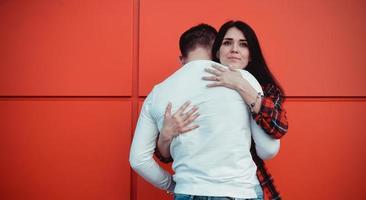 par dejtar och kramas förälskade i en solig dag - röd bakgrund foto