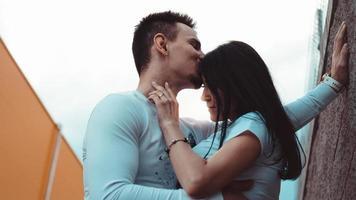 unga kärleksfulla par som står bredvid tegelväggen foto