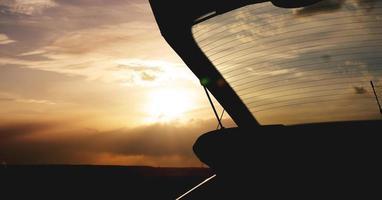 utomhus bil bagageutrymme vid solnedgången, foto mot solen