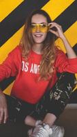 mode modell bär röd huva poserar på parkering foto