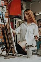 kvinnlig konstnär med pensel i konstverkstad foto
