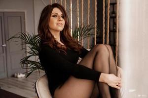 sexig kvinna i svarta strumpbyxor sitter på stolen foto