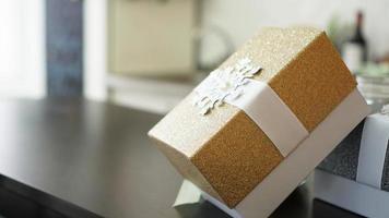 guld närvarande låda på träbord med suddig bakgrund foto