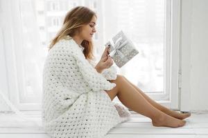 ung kvinna som sitter på fönsterbrädan med gåva hemma foto