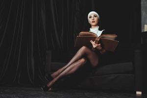 vacker ung nunna i religion svart kostym håller bibeln. religion foto