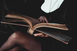nunna i religion svart kostym håller bibel. religion koncept foto