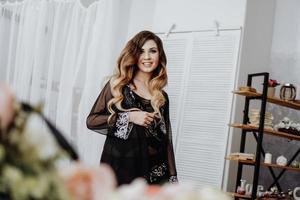 vacker sexig brun lockigt långt hår kvinna poserar i studion foto