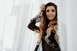 vacker sexig brun lockigt långt hår kvinna poserar i sängen foto