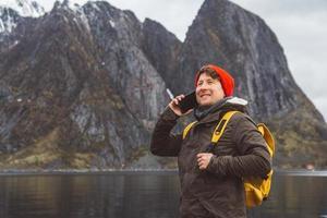 man pratar i telefon med en ryggsäck i naturen foto