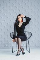 kvinna i en stol på en grå bakgrund foto