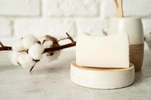 badtillbehör med bambuborstar och handgjord tvål på badhyllan foto
