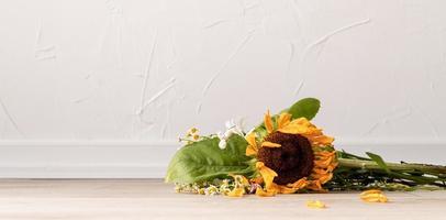 en bukett vissna blommor på golvet foto