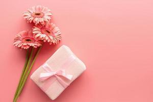rosa gerbera prästkragar bukett och rosa gåva på en rosa bakgrund foto