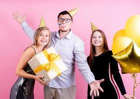 porträtt av glada vänner som firar födelsedagsfest, rosa bakgrund foto