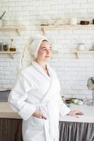 glad ung kvinna som applicerar ansiktsskrubba på hennes ansikte i sitt hemkök foto
