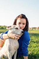 vacker ung kvinna som sitter i gräs och kramar sin hund i parken foto
