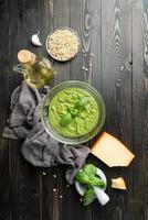färsk pesto i skål med ingredienser foto